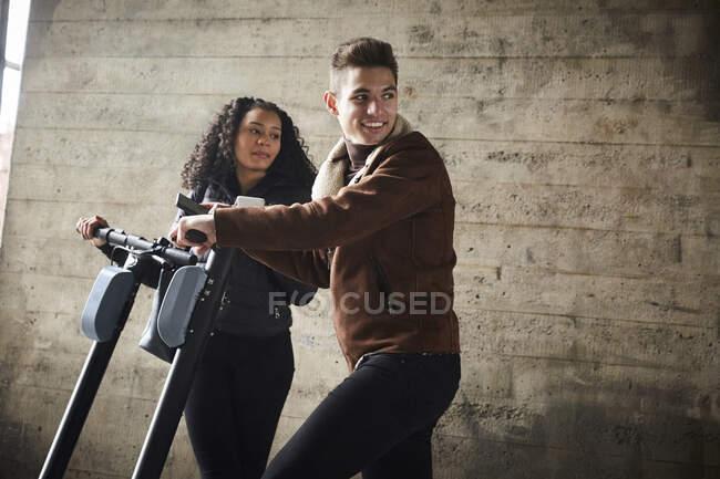Adolescente menino e menina com scooters empurrar elétrica olhando para longe enquanto está de pé contra a parede — Fotografia de Stock