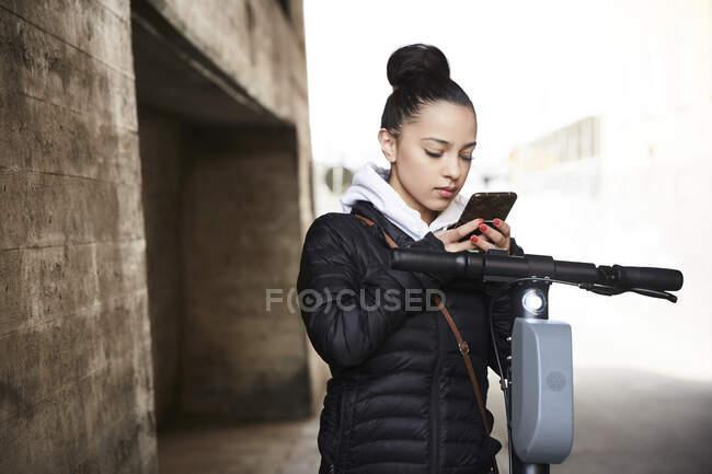 Menina adolescente com scooter elétrico empurrar usando telefone celular por parede — Fotografia de Stock