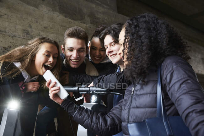 Teenage girl showing mobile phone to happy male and female friends — Stock Photo
