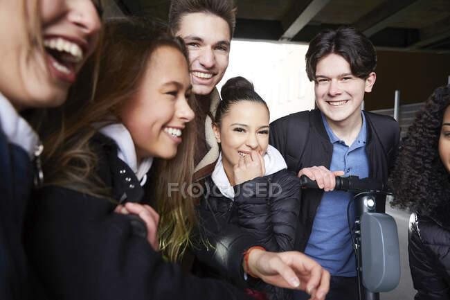 Glückliche männliche und weibliche Teenager-Freunde mit Elektroroller — Stockfoto