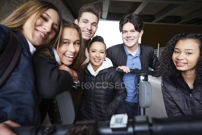 Portrait of smiling male and female teenage friends with electric push scooters below bridge — Stock Photo