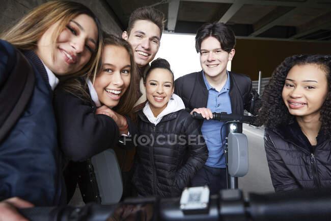Retrato de amigos adolescentes sonrientes masculinos y femeninos con scooters de empuje eléctricos debajo del puente - foto de stock