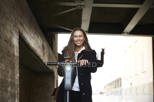 Portrait of smiling teenage girl with electric push scooter holding mobile phone below bridge — Stock Photo