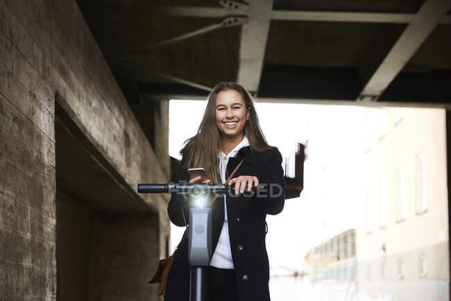 Retrato de sorrir adolescente com scooter elétrico empurrar segurando telefone celular abaixo da ponte — Fotografia de Stock