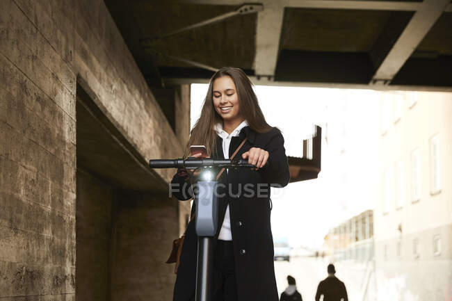 Smiling teenage girl with electric push scooter using mobile phone below bridge — Stock Photo
