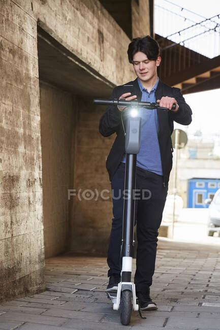 Menino adolescente com scooter elétrico empurrar usando telefone inteligente no caminho — Fotografia de Stock