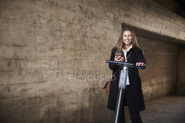 Retrato de sorrir adolescente com scooter elétrico empurrar pela parede — Fotografia de Stock