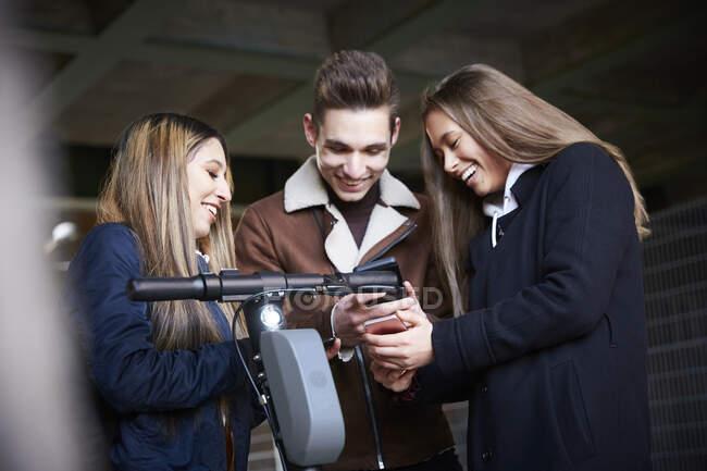 Felices amigos adolescentes masculinos y femeninos con scooter eléctrico mirando el teléfono inteligente debajo del puente - foto de stock