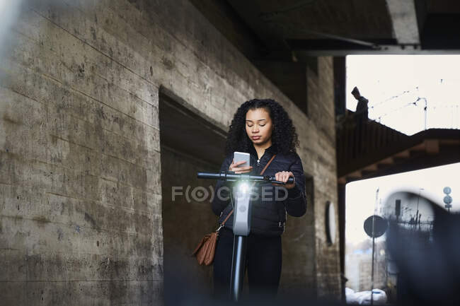 Menina adolescente com scooter elétrico empurrar usando telefone inteligente abaixo da ponte — Fotografia de Stock
