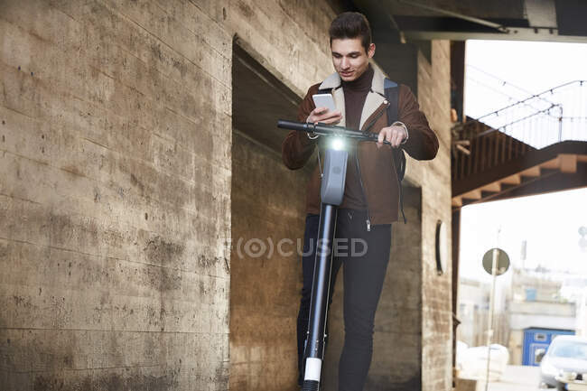 Teenage boy with electric push scooter using smart phone below bridge — Stock Photo