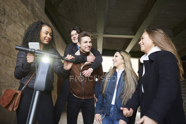 Smiling male and female teenage friends with electric push scooter on footpath below bridge — Stock Photo