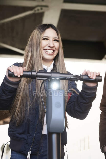 Smiling teenage girl with electric push scooter standing by male friend below bridge — Stock Photo