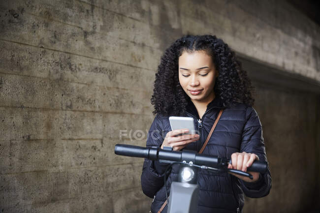 Teenage girl with electric push scooter using mobile phone by wall — Stock Photo