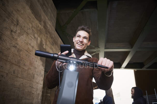 Happy teenage boy with electric push scooter looking away while holding mobile phone below bridge — Stock Photo