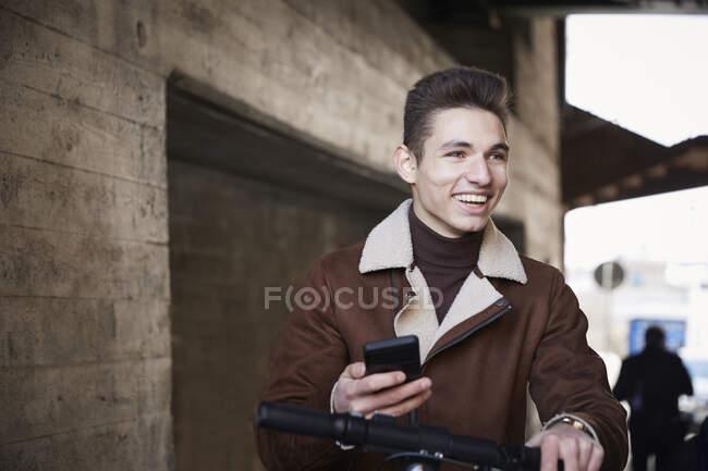 Sorrindo adolescente menino com scooter elétrico empurrar olhando para longe enquanto segurando telefone celular abaixo da ponte — Fotografia de Stock