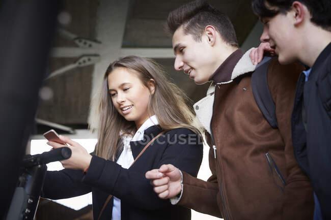 Teenager sieht Freundin mit Handy unter Brücke an — Stockfoto