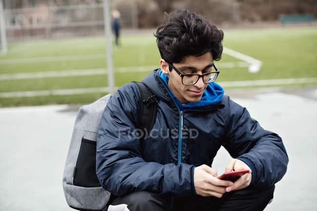 Adolescente niño usando el teléfono móvil mientras se sienta contra el campo de fútbol en la ciudad durante el invierno - foto de stock