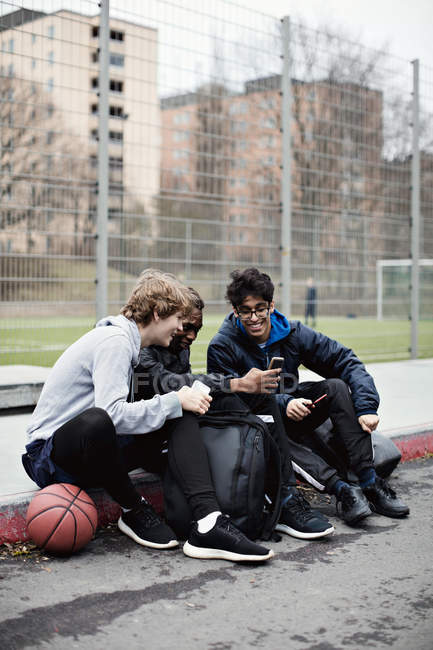 Full length of social media addicted friends wearing warm clothing while sitting on sidewalk after basketball practice d — Stock Photo