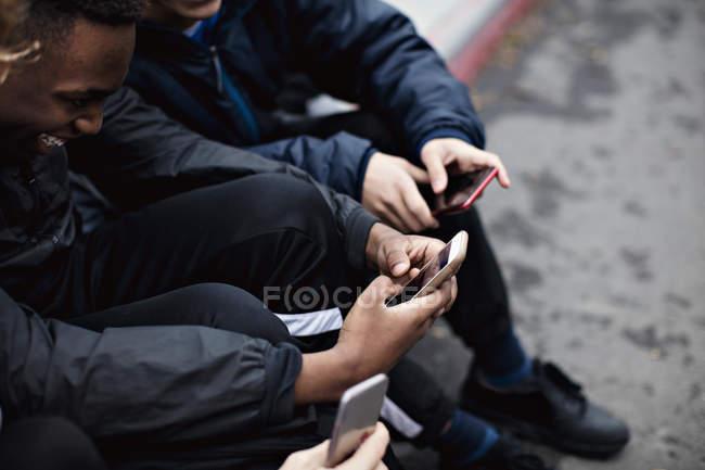 Mídia social viciado amigos do sexo masculino sentados na rua na cidade durante o inverno — Fotografia de Stock