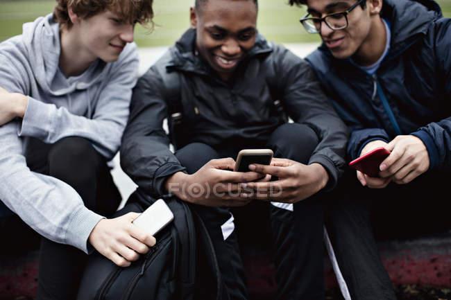 Amigos felizes usando as mídias sociais enquanto se sentam na calçada na cidade — Fotografia de Stock