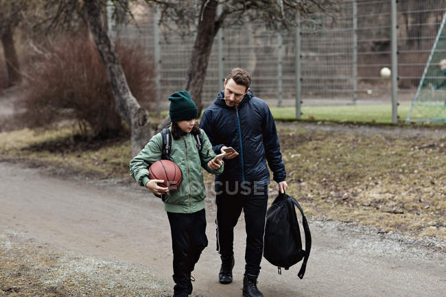Father and son using mobile phones while walking on street during winter — Stock Photo