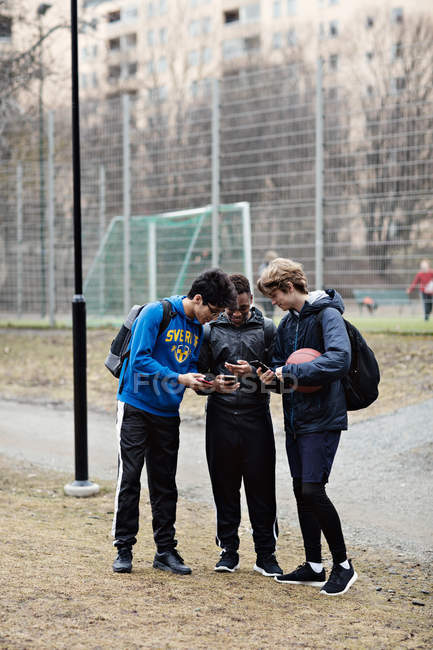 Full length of social media addicted friends wearing sports clothing while using mobile phones on playing field — Stock Photo