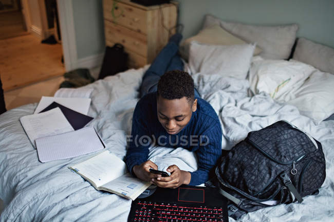 Vista ad alto angolo di adolescente distratto utilizzando il telefono cellulare mentre sdraiato sul letto da libri a casa — Foto stock