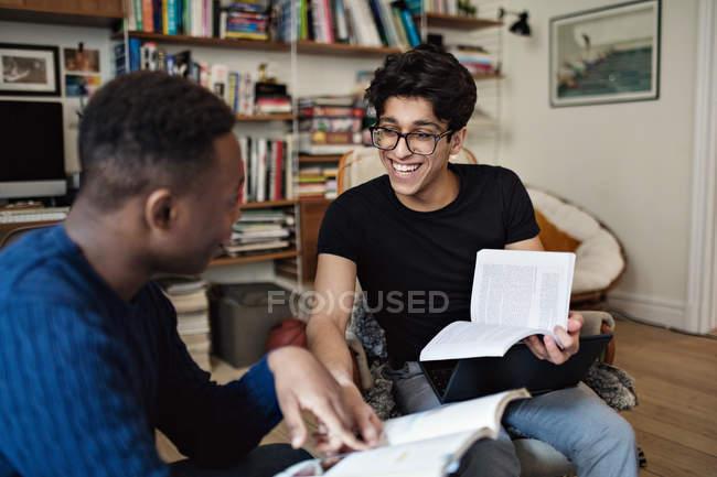 Веселі друзі вивчають, сидячи у вітальні в домашніх умовах — стокове фото