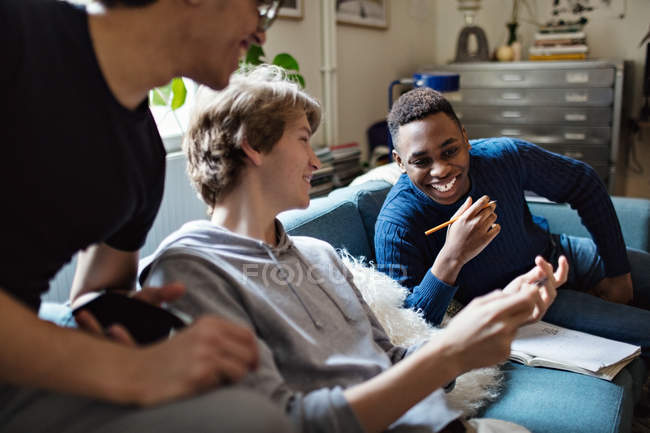 Smiling teenage boy showing mobile phone to friends on sofa while studying at home — Stock Photo