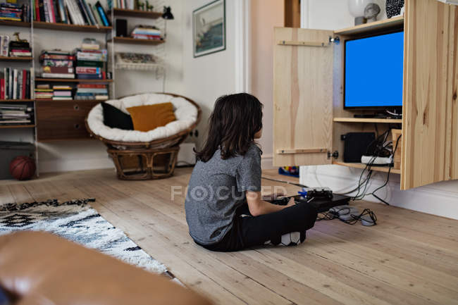 Side view of boy playing video game while sitting on hardwood floor at home — Stock Photo