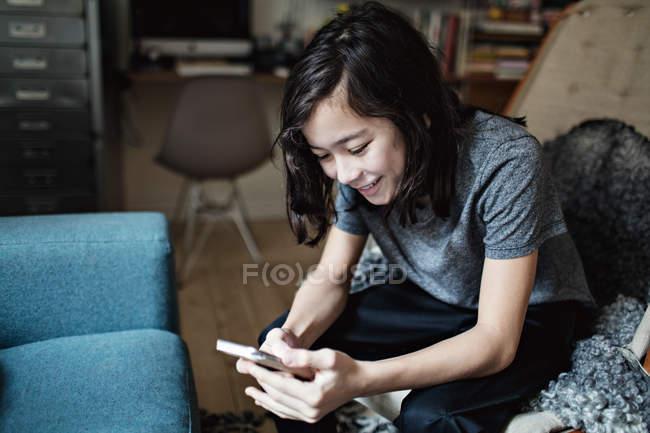 Social mídia viciado sorrindo menino usando telefone celular enquanto sentado em casa — Fotografia de Stock