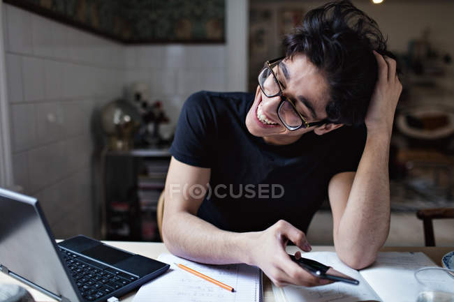 Cheerful social media addicted Teenage Boy using mobile phone while doing homework — Stock Photo