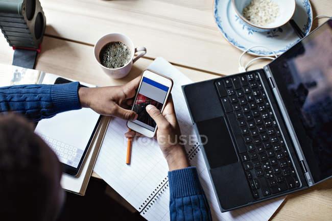 Vista de ángulo alto del adolescente usando el teléfono móvil mientras estudia en la mesa en casa - foto de stock