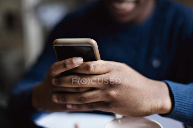 Social media addicted teenage boy using smart phone while studying at home — Stock Photo