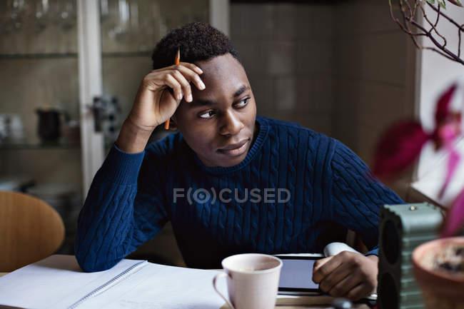 Miúdo adolescente atencioso olhando para longe enquanto faz trabalhos de casa na mesa — Fotografia de Stock