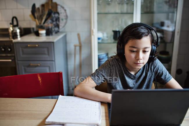 Menino usando fones de ouvido enquanto usa laptop durante os trabalhos de casa em casa — Fotografia de Stock