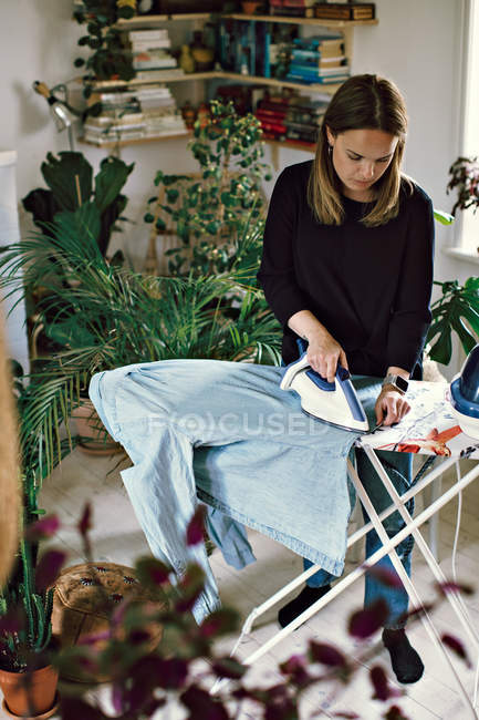 Full length of woman ironing shirt on board in room at home — Stock Photo