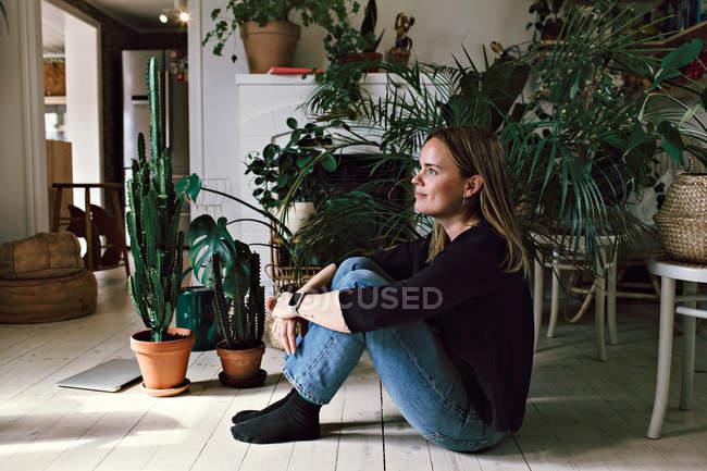 Volle Seitenansicht der nachdenklichen Frau, die zu Hause auf Hartholzboden sitzt — Stockfoto