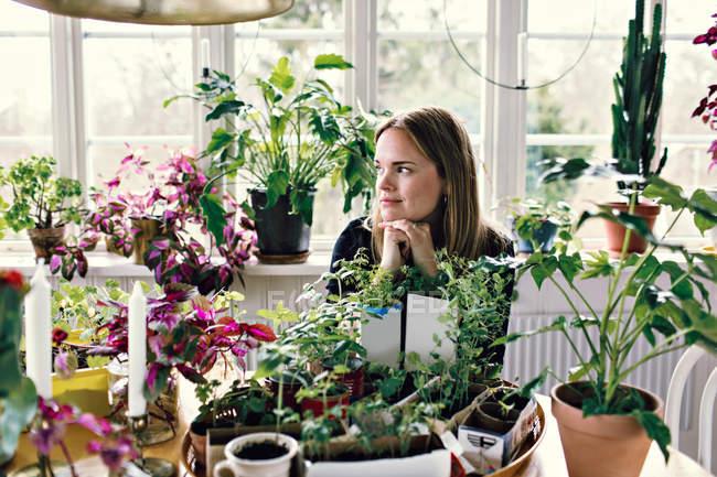 Nachdenkliche mittlere erwachsene Frau sitzt am Tisch und schaut weg gegen Fenster im Zimmer — Stockfoto