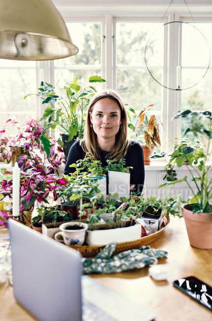 Retrato da mulher que jardina na tabela de encontro ao indicador — Fotografia de Stock