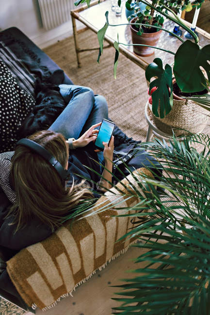 High angle view of woman using smart phone while listening music at home — Stock Photo