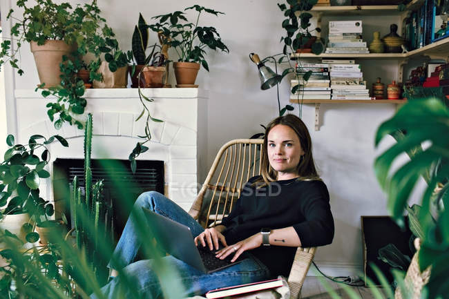 Portrait of woman sitting with laptop on armchair in room at home — Stock Photo