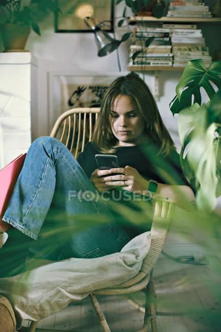 Женщина текстовых сообщений через мобильный телефон в комнате дома — стоковое фото