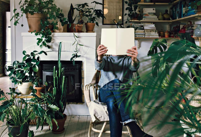 Man sitting on armchair reading book amidst plants in room at home — Stock Photo