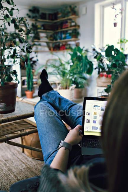 Longitud completa de la mujer navegando por la red en el ordenador portátil mientras se relaja en casa - foto de stock