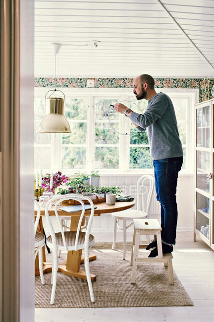 Full length side view of man standing on stool photographing plants in room at home — Stock Photo