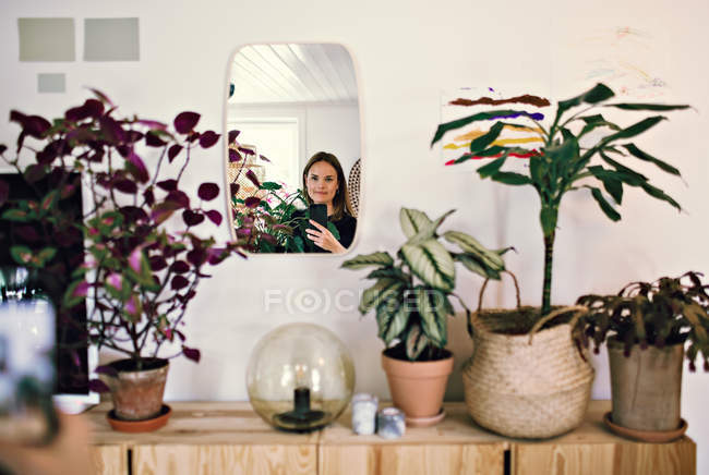 Reflection of woman in mirror by potted plants at home — Stock Photo