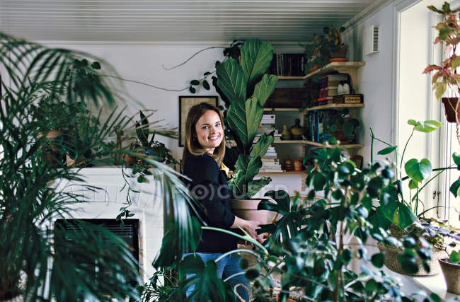 Portrait of smiling woman carrying potted plant at home — Stock Photo