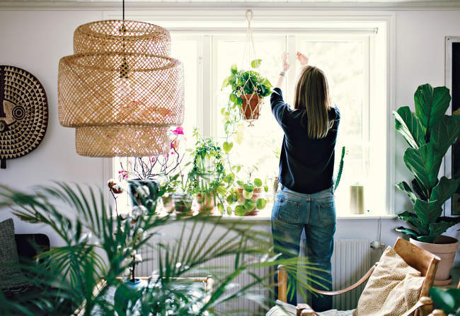 Rear view of woman closing window in room at home — Stock Photo