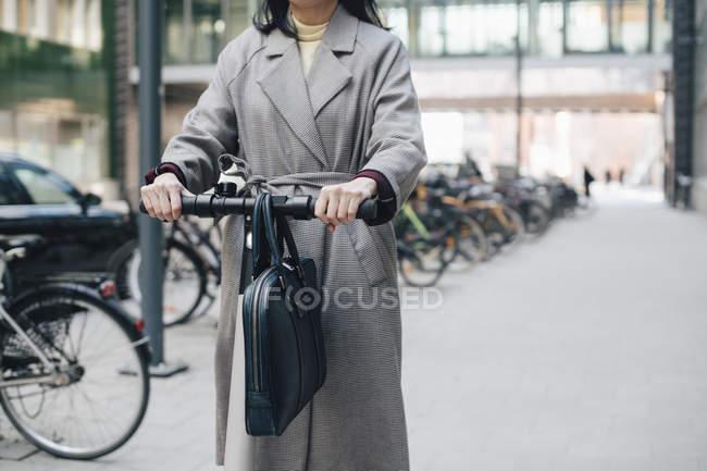 Midsection de mujer de negocios montando scooter de empuje eléctrico en el sendero en la ciudad - foto de stock